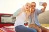 Paar auf Motorhaube eines Auto sitzend ein Foto machend