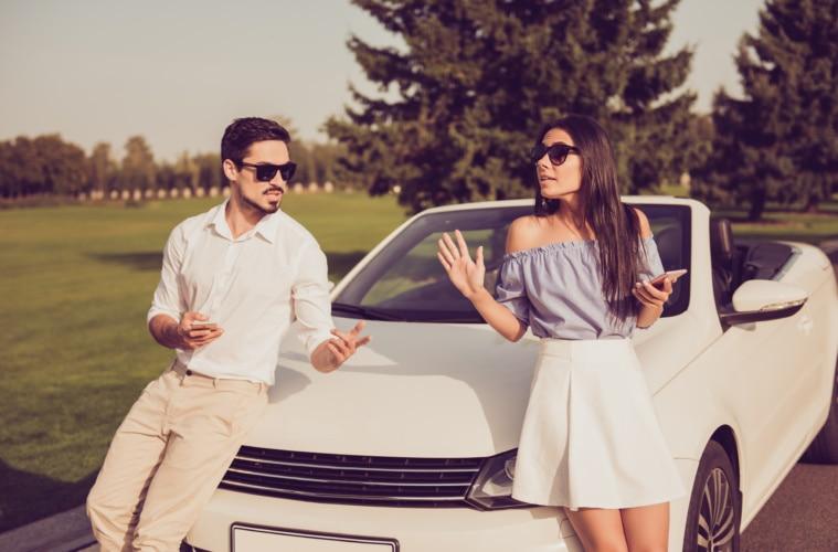 Paar streitet im Urlaub vor einem Auto