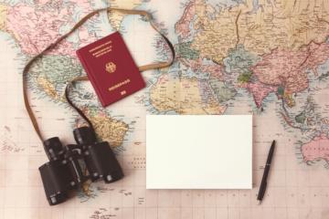 Reisepass mit Fernglas auf Weltkarte