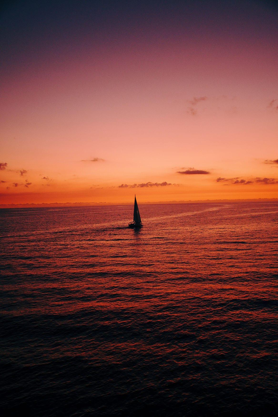 Ein Schiff segelt vor Gozo in en Sonnenuntergang