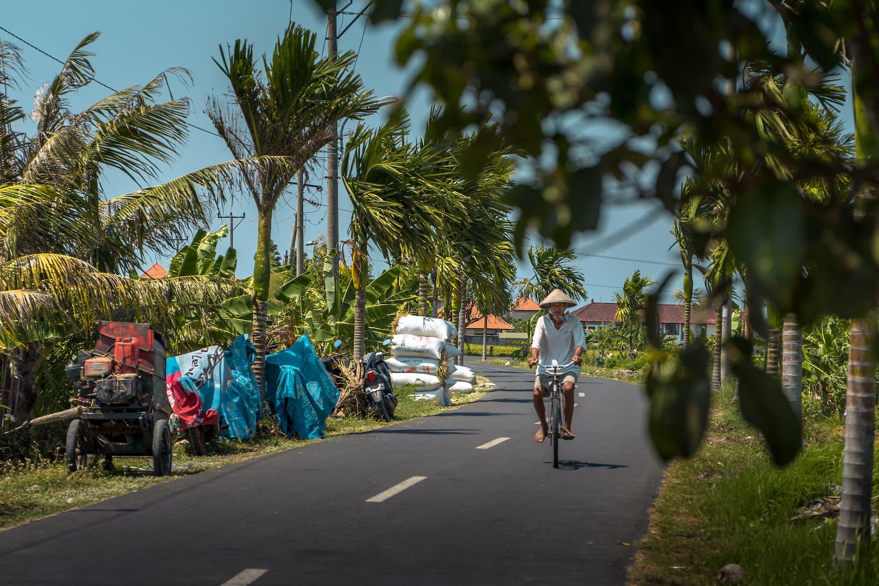 Asiatischer Mann fährt Fahrrad über ruhige Straße auf Bali