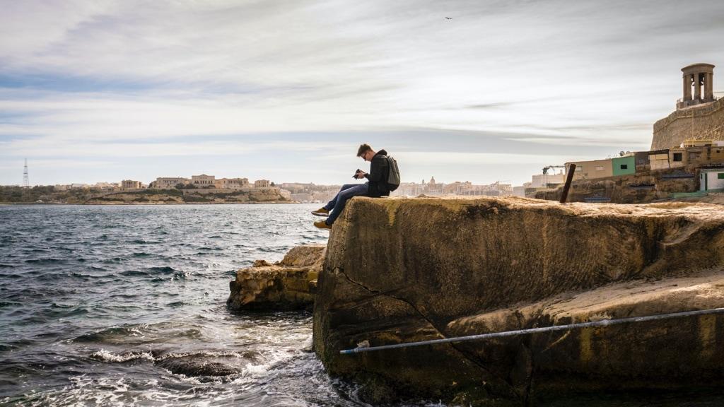 Mann mit einer Kamera sitzt auf einem Felsen am Meer in valletta
