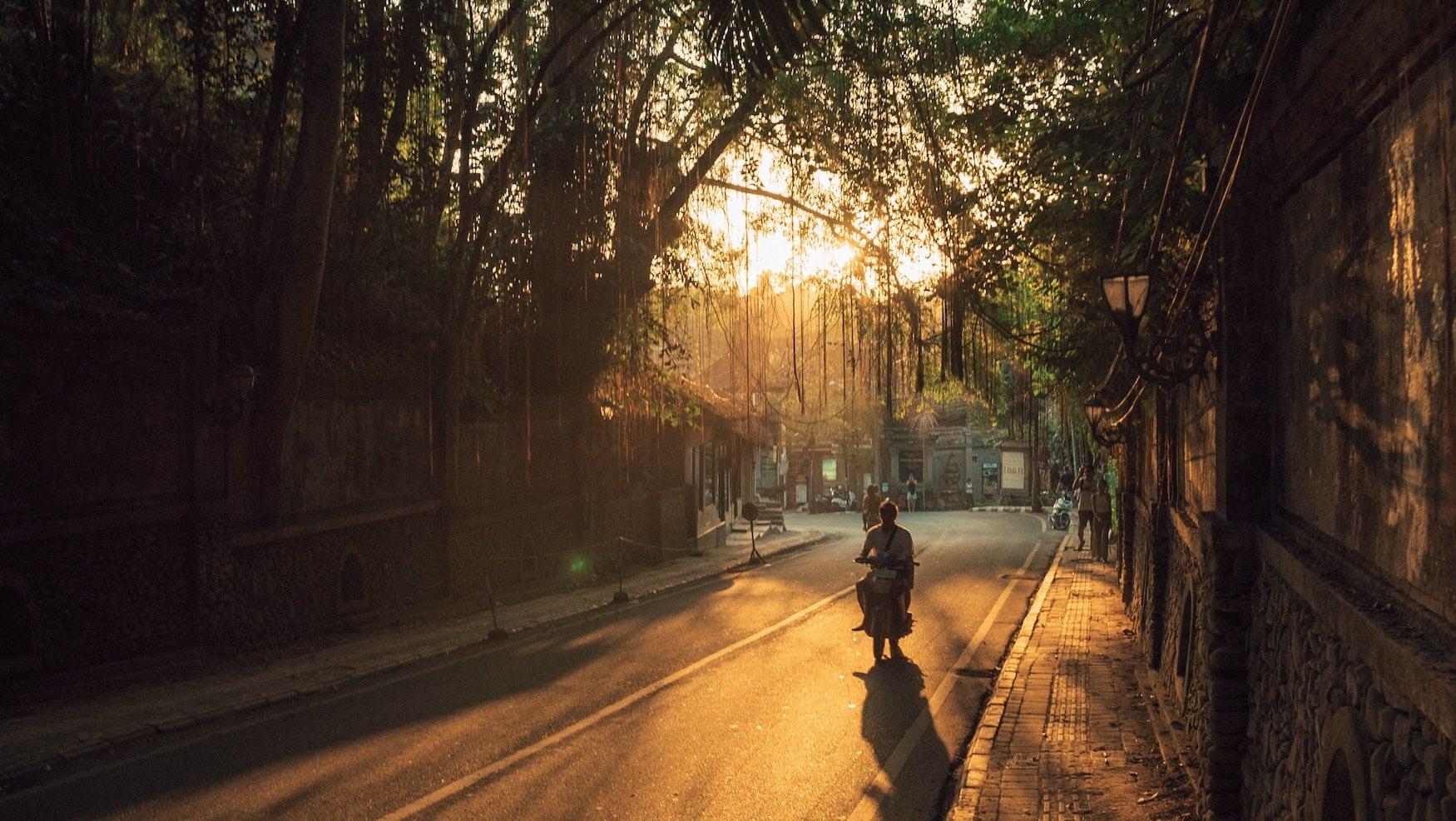 Mann fährt auf Motorrad in den Sonnenuntergang