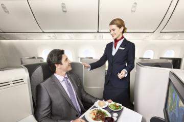 Passagier und Flugbegleiterin in der Air Canada Signature Class