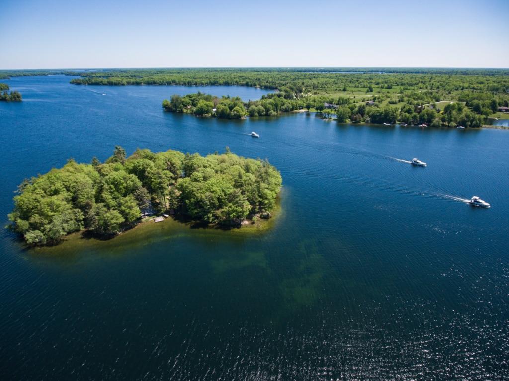 Aerial of island and three Le Boat Horizon houseboats, Big Rideau Lake, Ontario, Canada