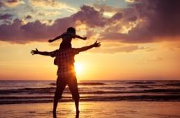 Vater und Sohn am Strand bei Sonnenuntergang