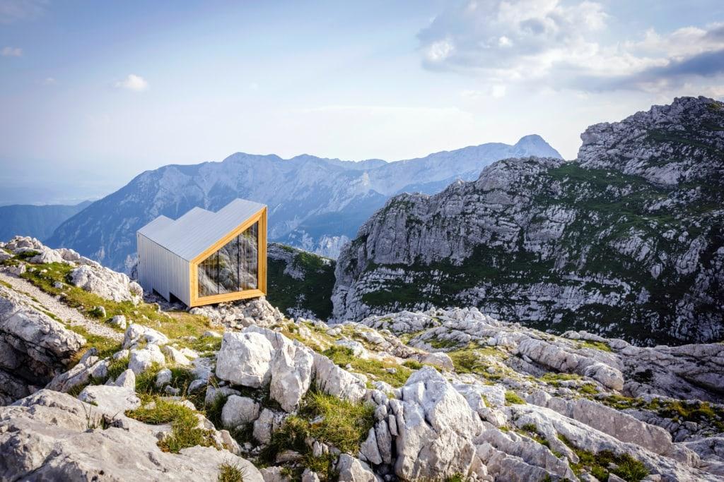 Links sieht man die dreizackige Alpine Shelter, dahinter machen sich die mächtigen Berge der Kamniker Alpen breit.