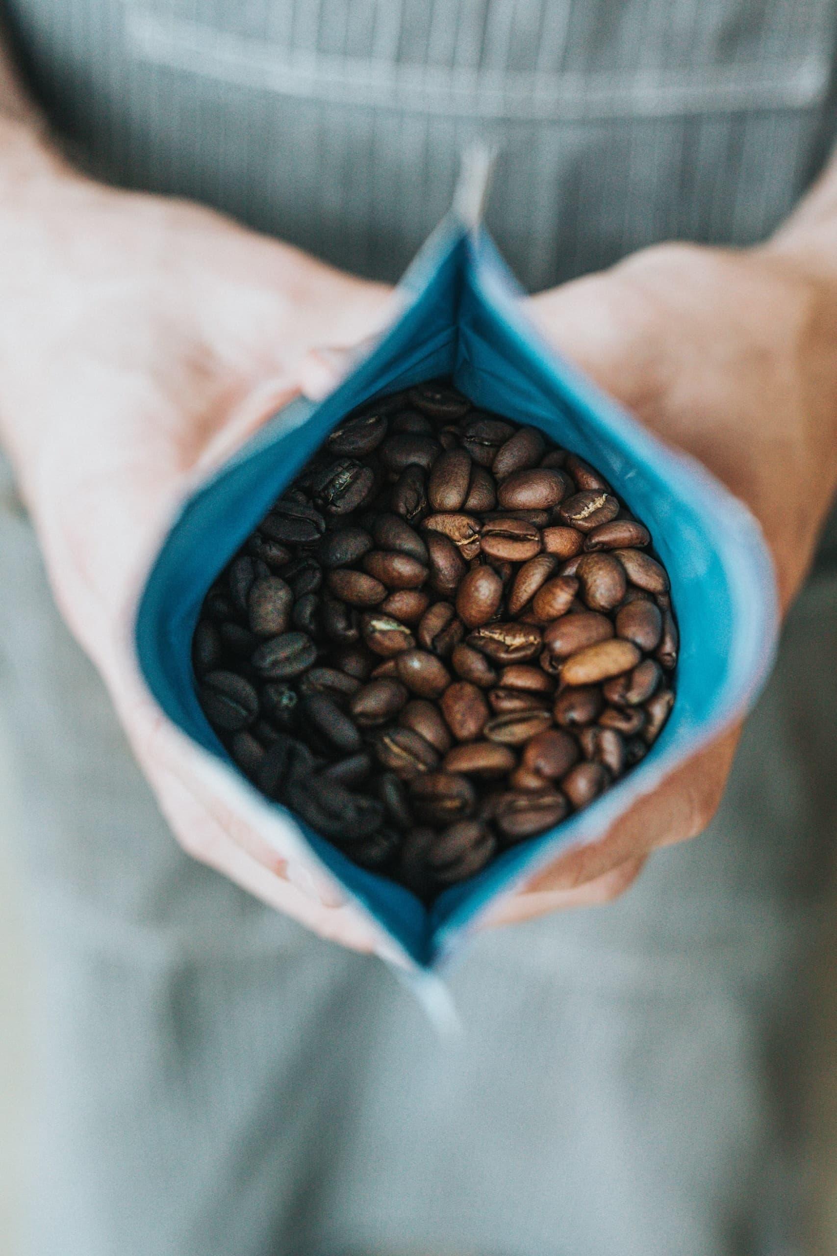 Mann hält Packung mit frisch geröstetem Kaffee in der Hand