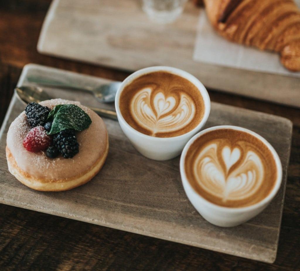 Zwei Kaffeetassen und ein Süßgebäck