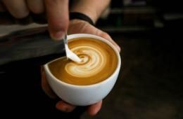 Person hält Kaffeetasse in der Hand und schüttet mit der anderen geschäumte Milch hinein