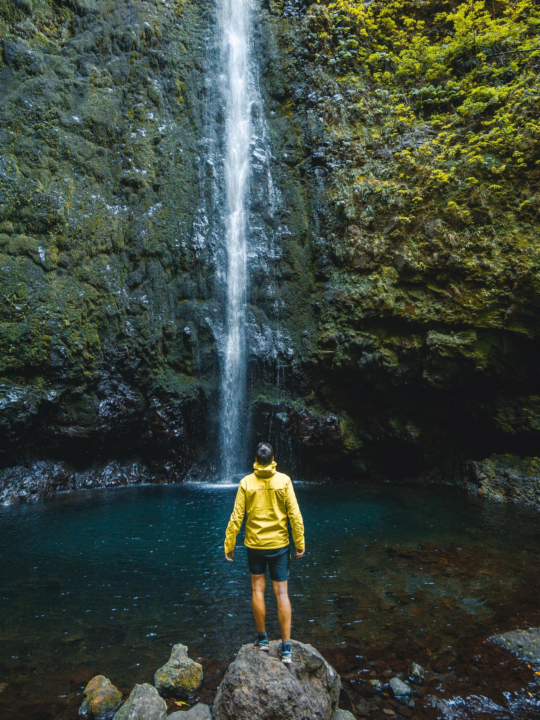 Mann mit gelber Regenjacke steht an Fuße eines Wasserfalls