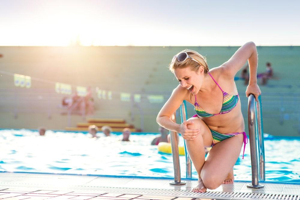 Junge Frau steigt mit Schmerzen aus dem Swimmingpool