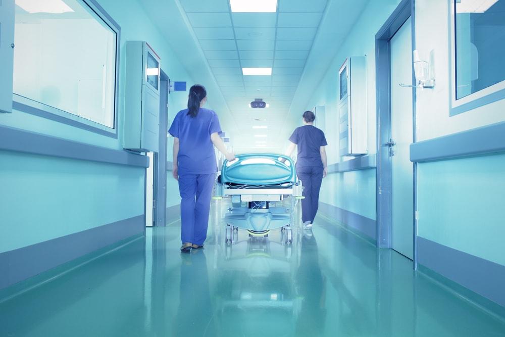 Zwei Krankenhauspfleger gehen einen Gang entlang
