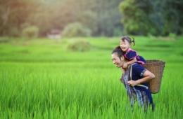 Frau mit Kind auf Rücken in Laos