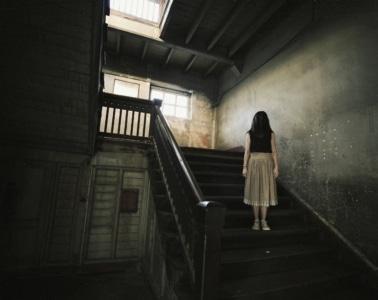 Orte zum Gruseln: Mädchen auf Treppe in altem Haus