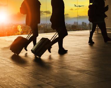 Passagiere mit Koffer im Schlepptau im Flughafen
