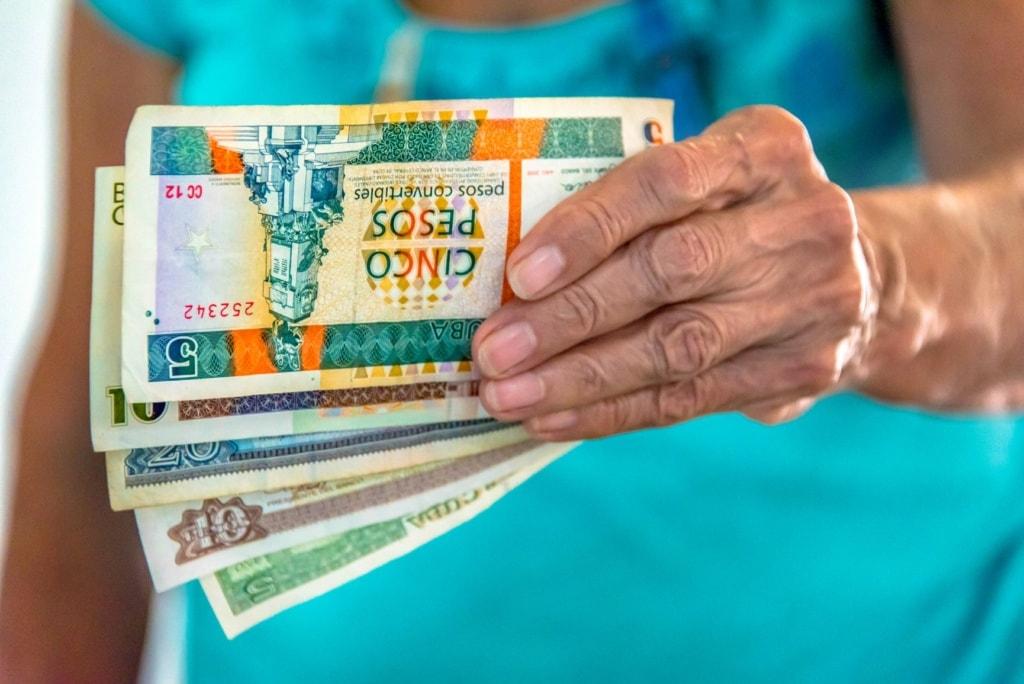 Frau hält kubanische Pesos in der Hand