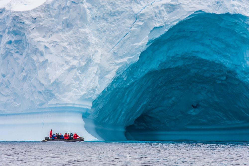 Touristen auf einem Zodiac vor einem Eisberg in der Antarktis