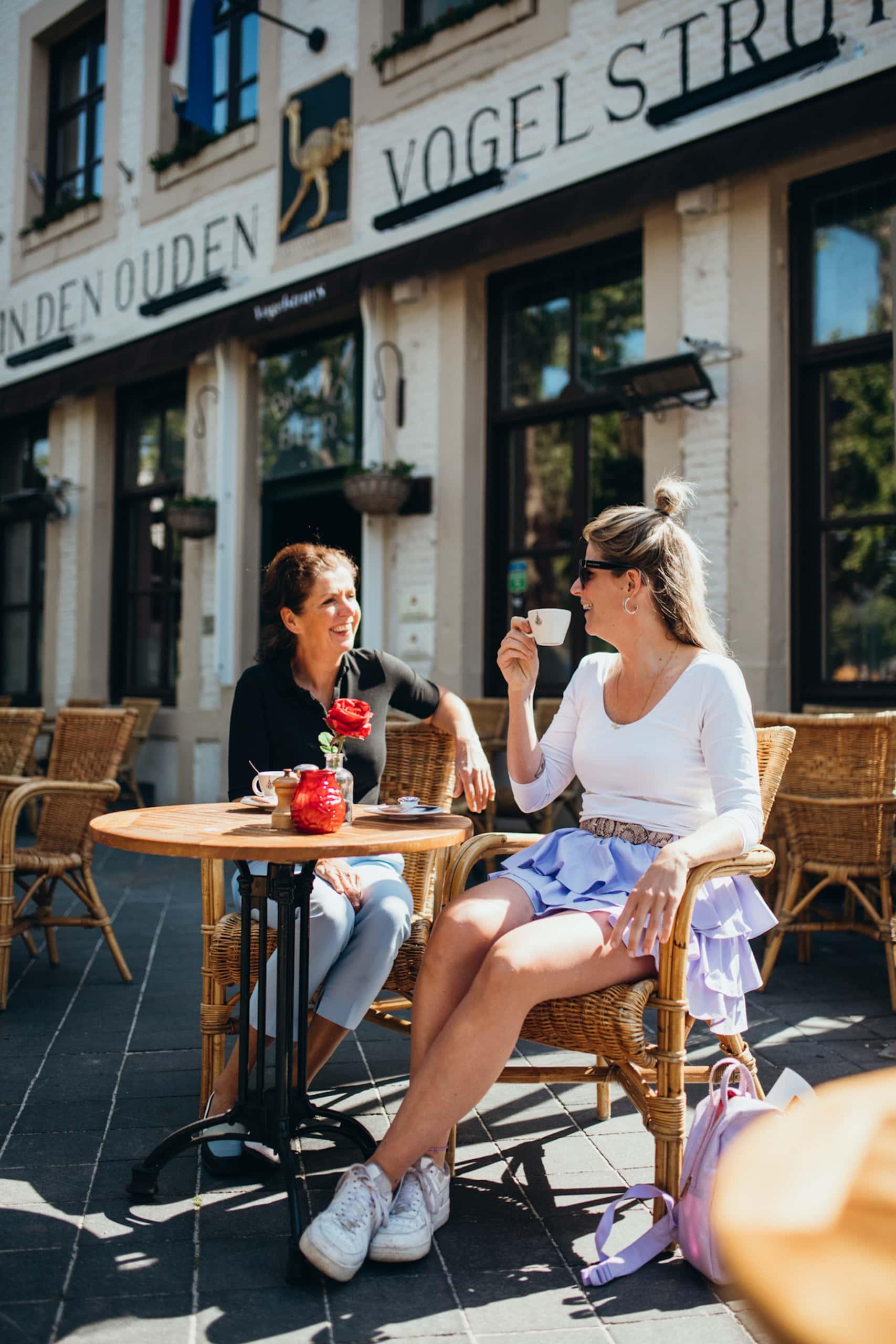 Zwei Frauen sitzen vor Café an einem sonnigen Tag