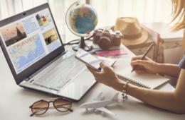 Frau plant ihren Urlaub am Laptop mit Weltkugel, Sonnenbrille, Sonnenhut am