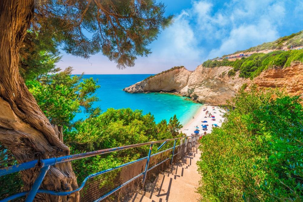 Stufen aus Gestein, zwischen Pinienbäumen hinunter zum Strand