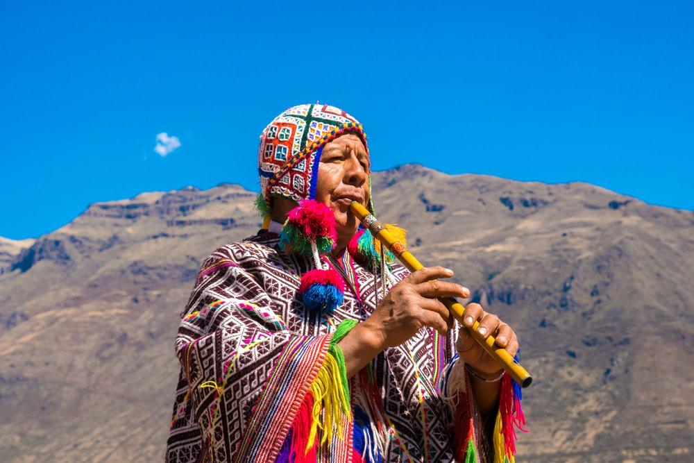 Einheimischer in Cusco in Peru mit traditioneller Kleidung und Flöte
