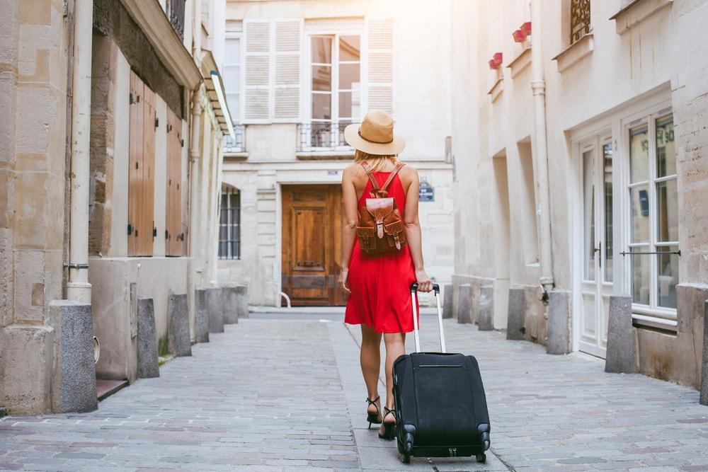 Frau in rotem Kleid mit Rollkoffer durch Straße in europäischer Stadt
