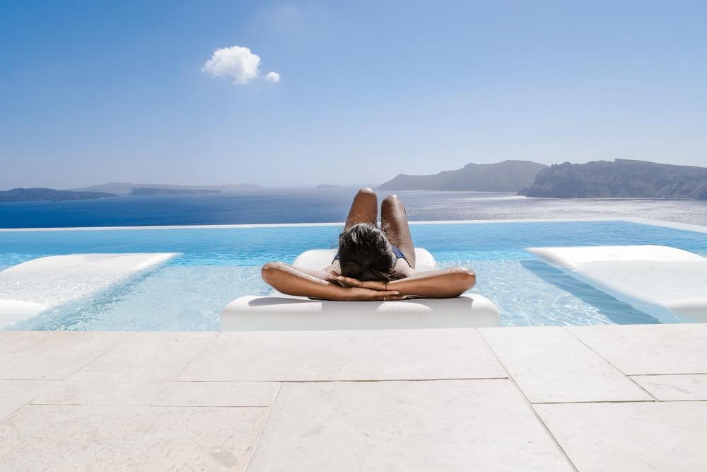 Frau liegt am Pool mit Meerblick
