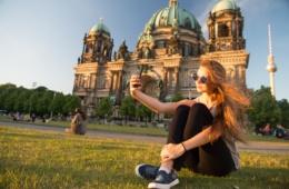 Junge Frau macht Selfie auf Wiese in Berlin
