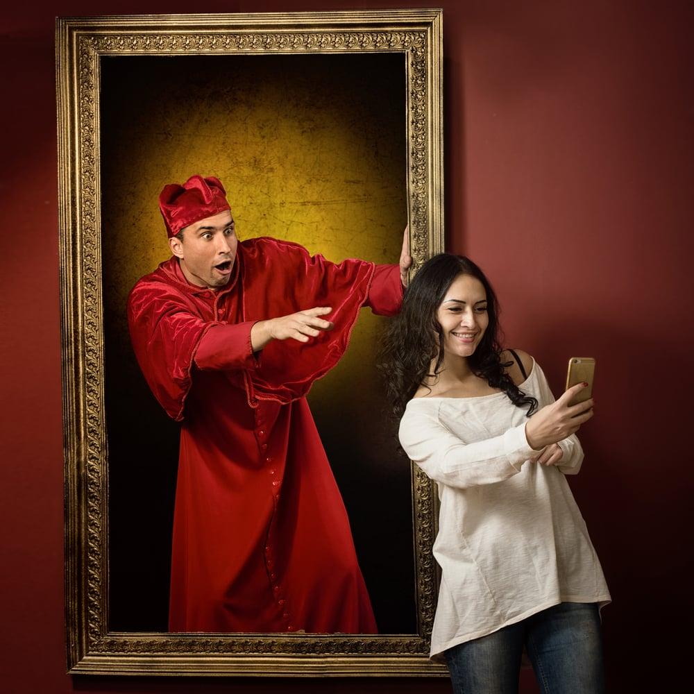 Frau macht Selfie vor Kunstwerk im Museum
