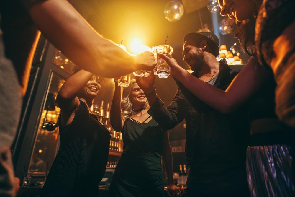 Gruppe von jungen Leuten stößt in Bar an