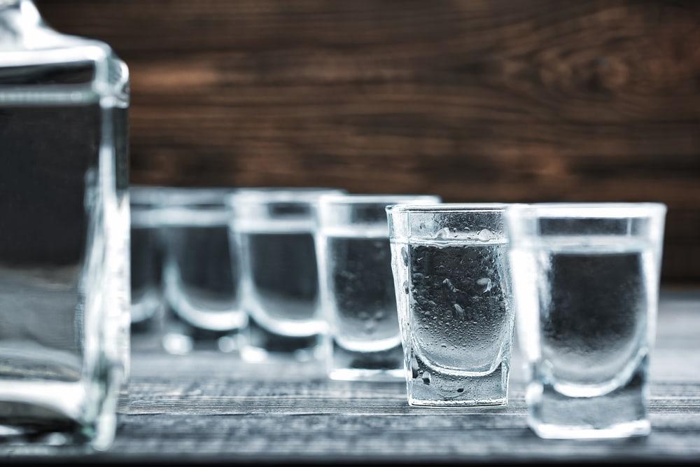 Eine Reihe mit vollen Wodkagläsern vor dunklem Hintergrund