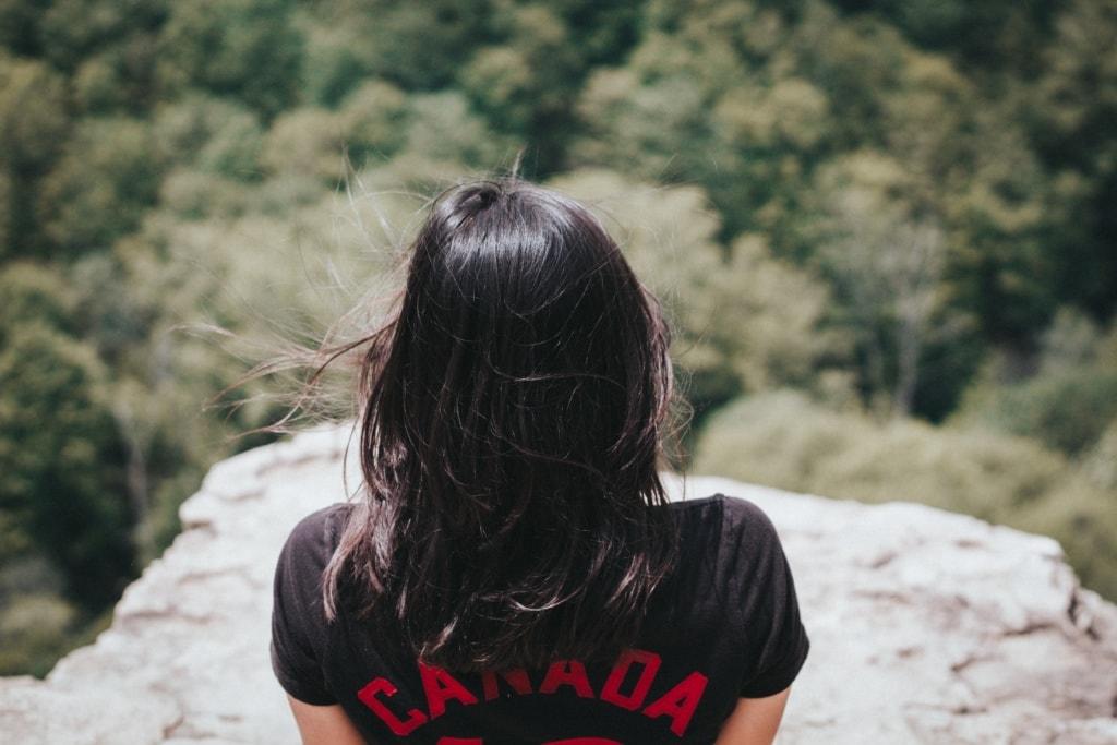 Frau auf Klippe, genießt Ausblick