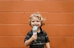 Ein kleiner Junge steht vor einer orangefarbenen Wand und schleckt ein Eis.