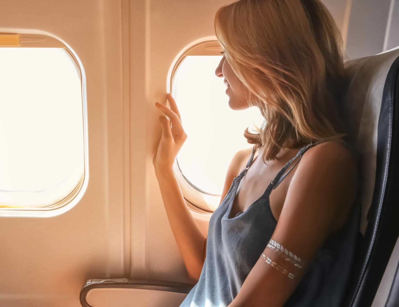 Junge blonde Frau in Flugzeug lächelnd aus dem Fenster schauend.