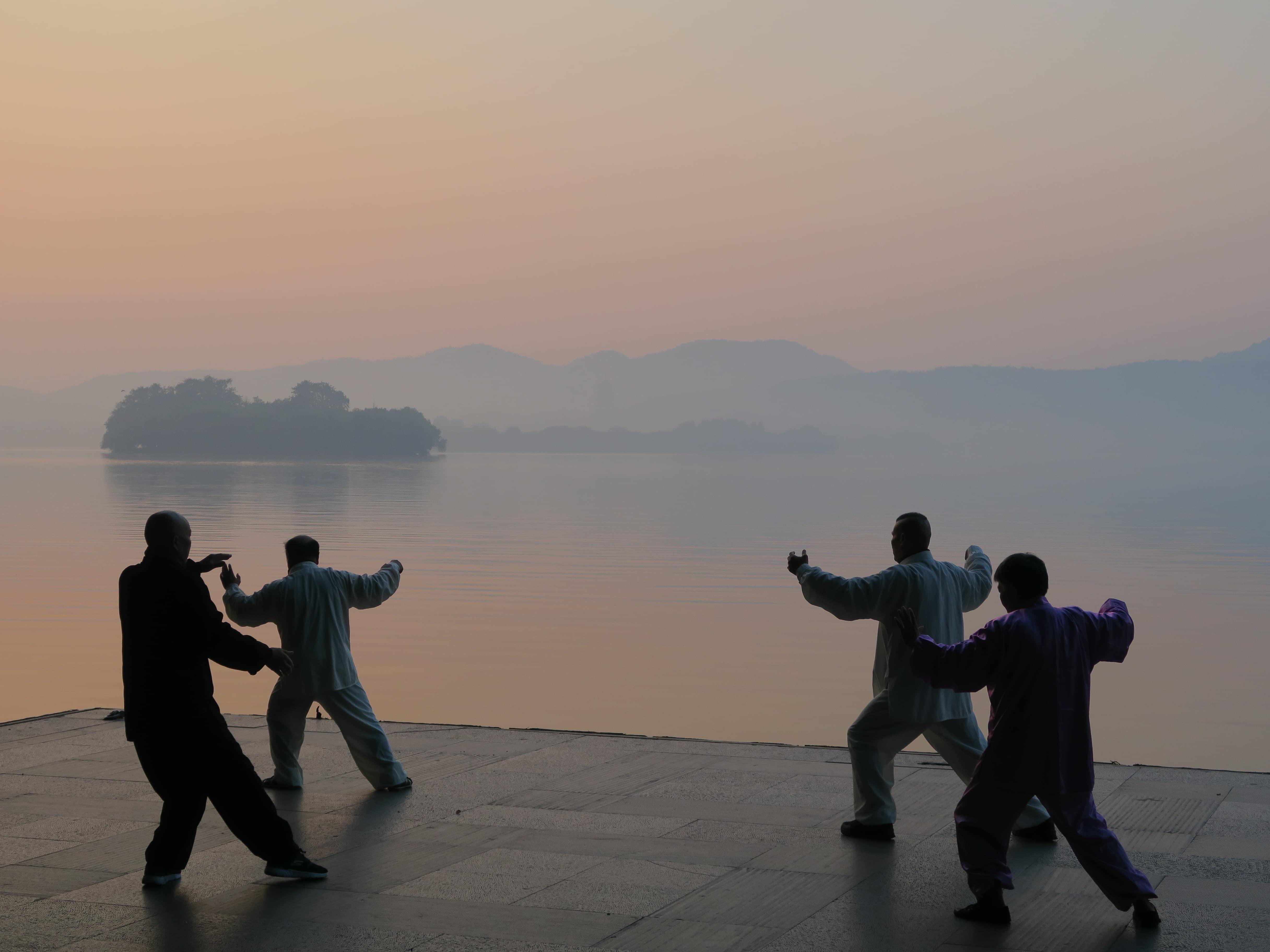 Vier Tai Chi-Kämpfer bei Sonnenaufgang an See