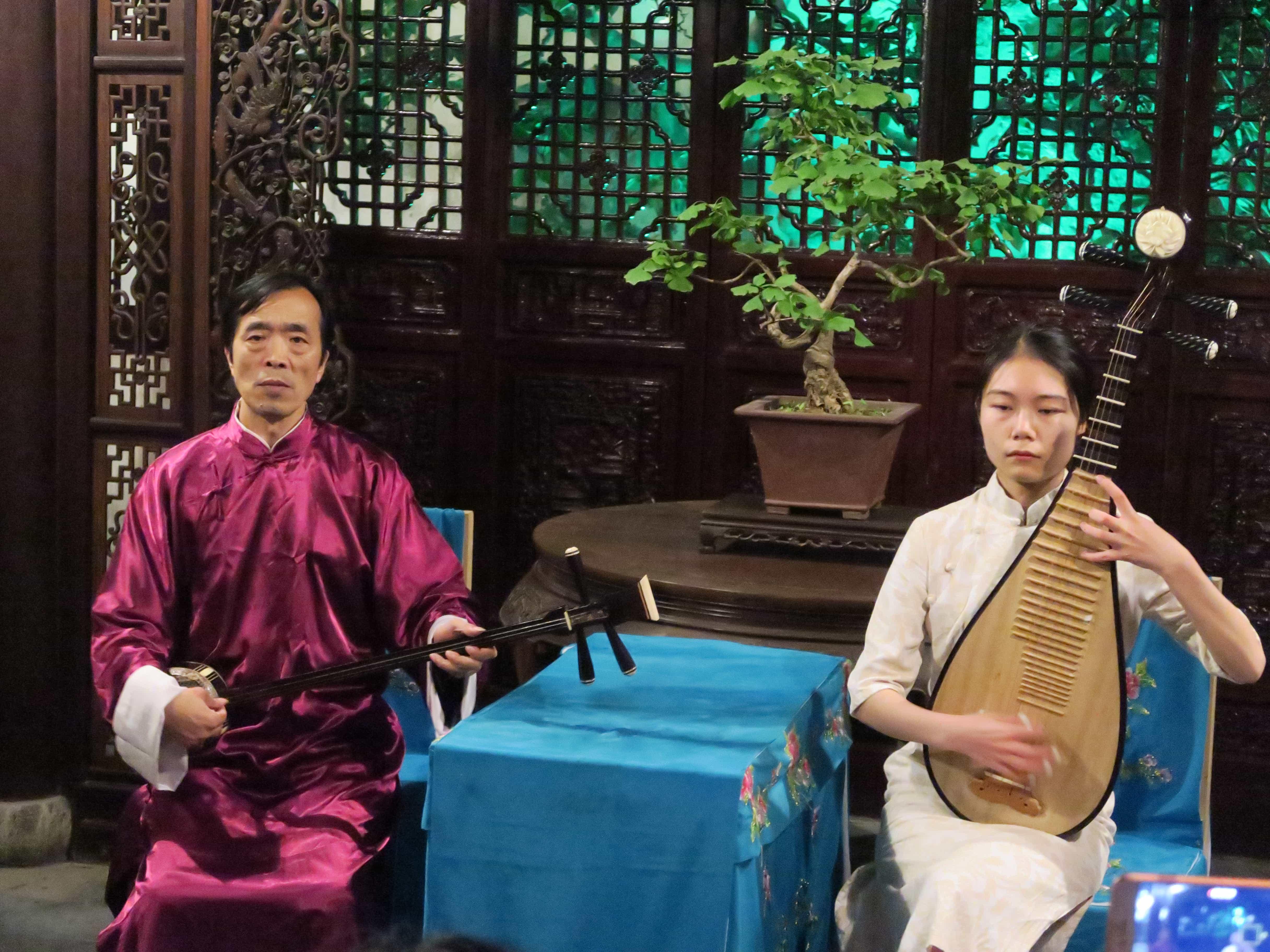 Zwei Chinesen (Mann und Frau) spielen in traditionellem Pavillion Instrumente