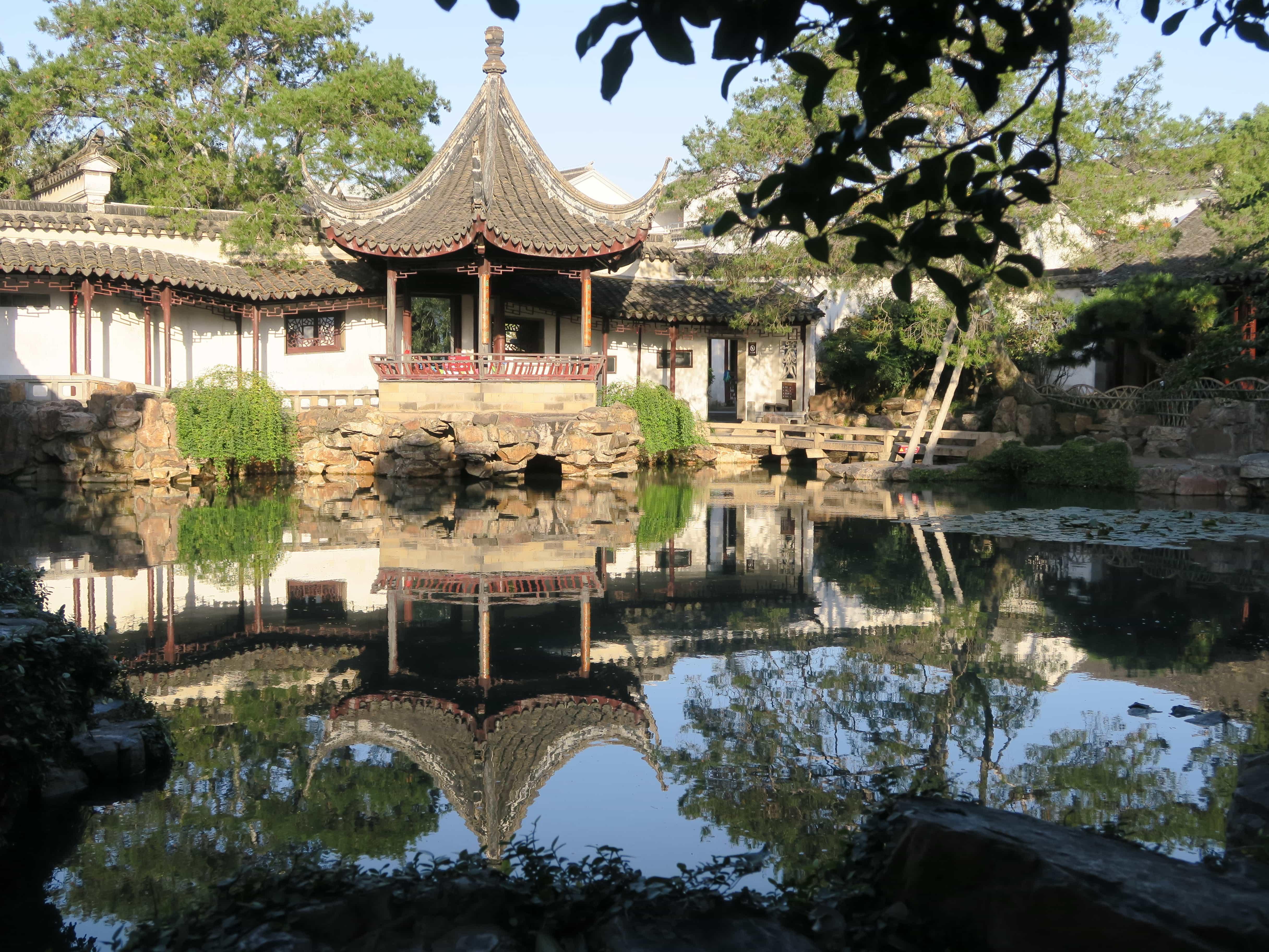 Pavillon am Fuße eines Sees mit Spiegelung der Landschaft