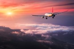 Flugzeug im roten Sonnenuntergang über Wolken und Meer