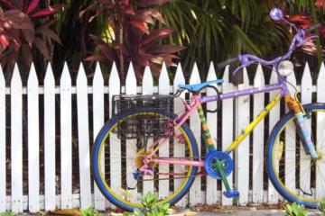 Buntes Fahrrad steht vor einem Holzzaun