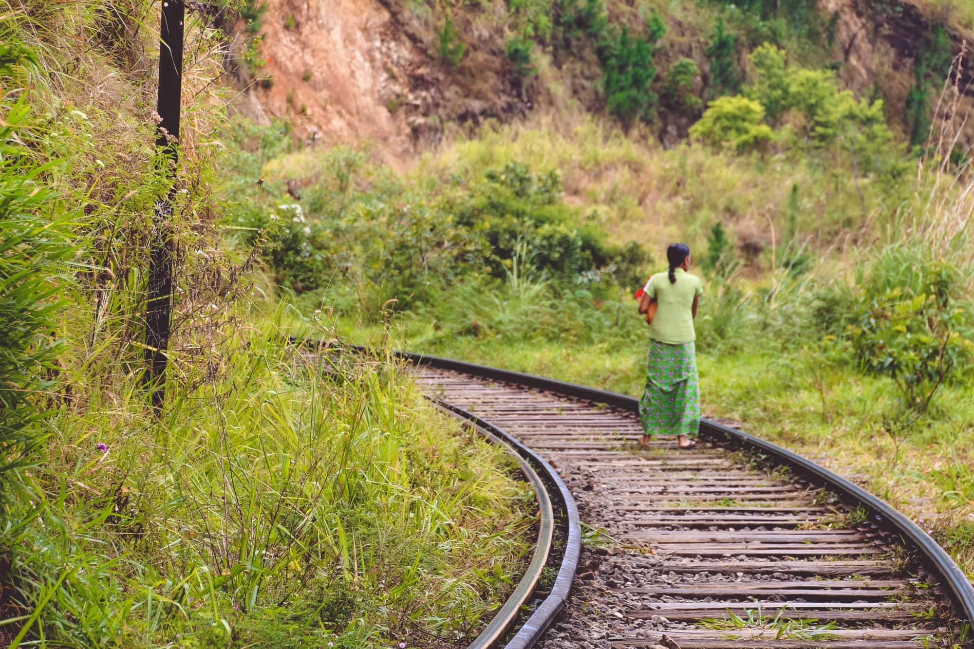Einheimische Frau spaziert auf den Schinen in Ella, Sri Lanka