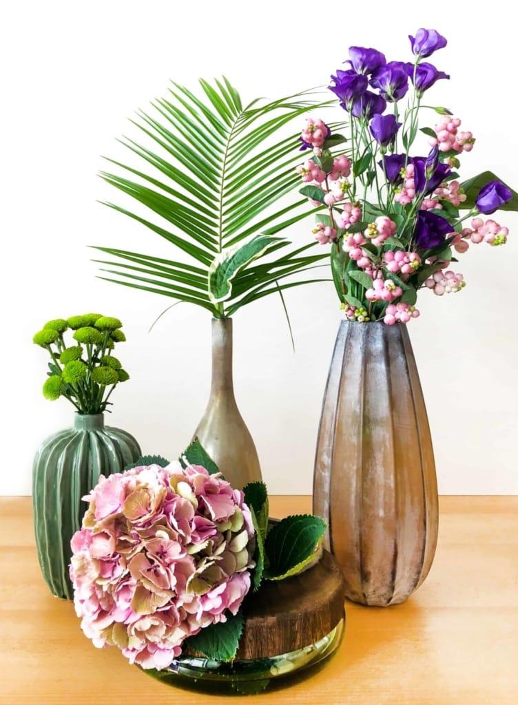 vier Vasen in Naturtönen und verschiedenen Formen sowie Blumen