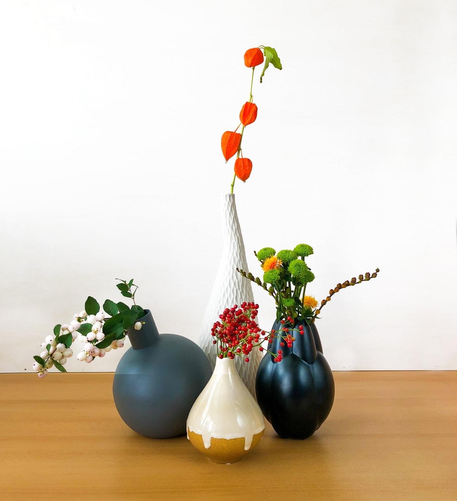 Vier verschiedene Vasen mit unterschiedlichen Blumen