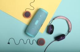 Kopfhörer und Boxen vor türkiser und gelber Pappe