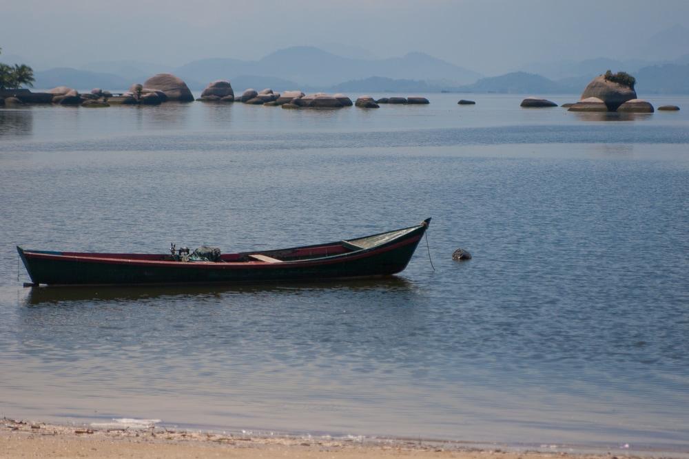 Kleines Holzboot in seichtem tropischen Wasser mit Felsen