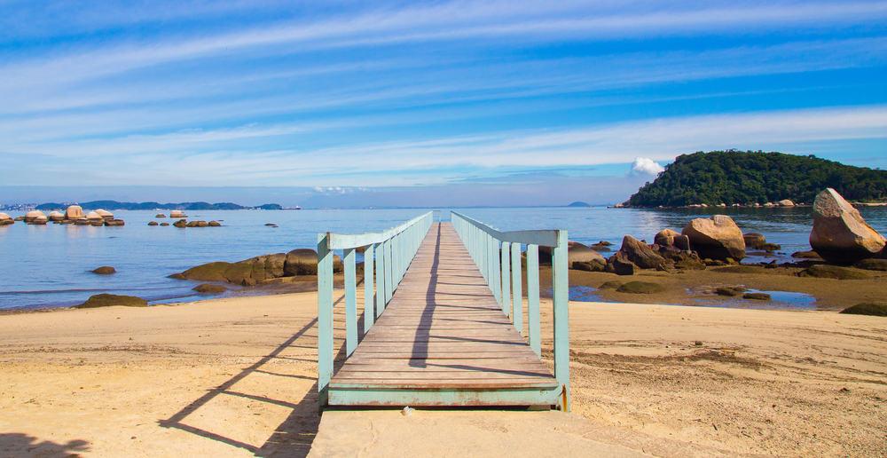 Schmale Holzbrücke führt von tropischem Strand ins Wasser