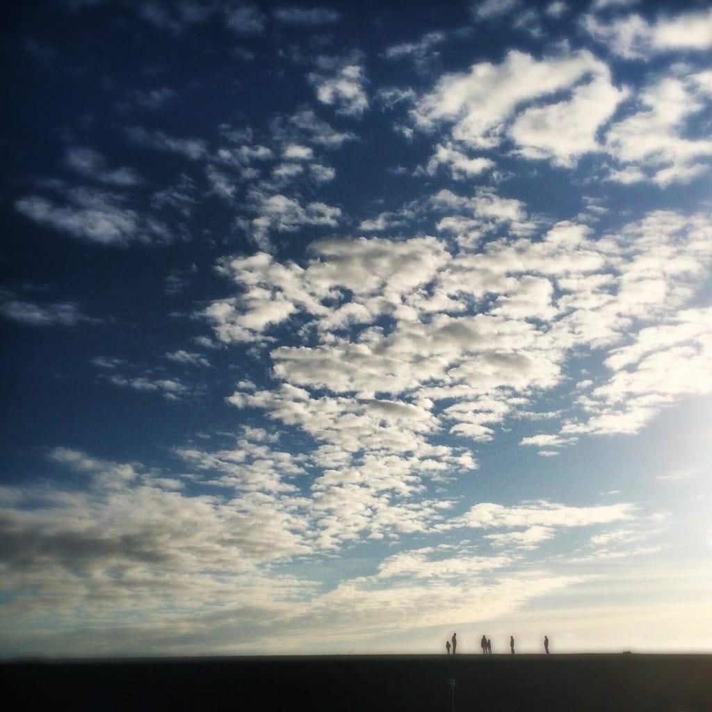 Menschen am Meer in Büsum vor gewaltiger Himmelkulisse