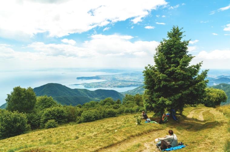 Leute machen auf Wanderpfad Rast und schauen auf den See