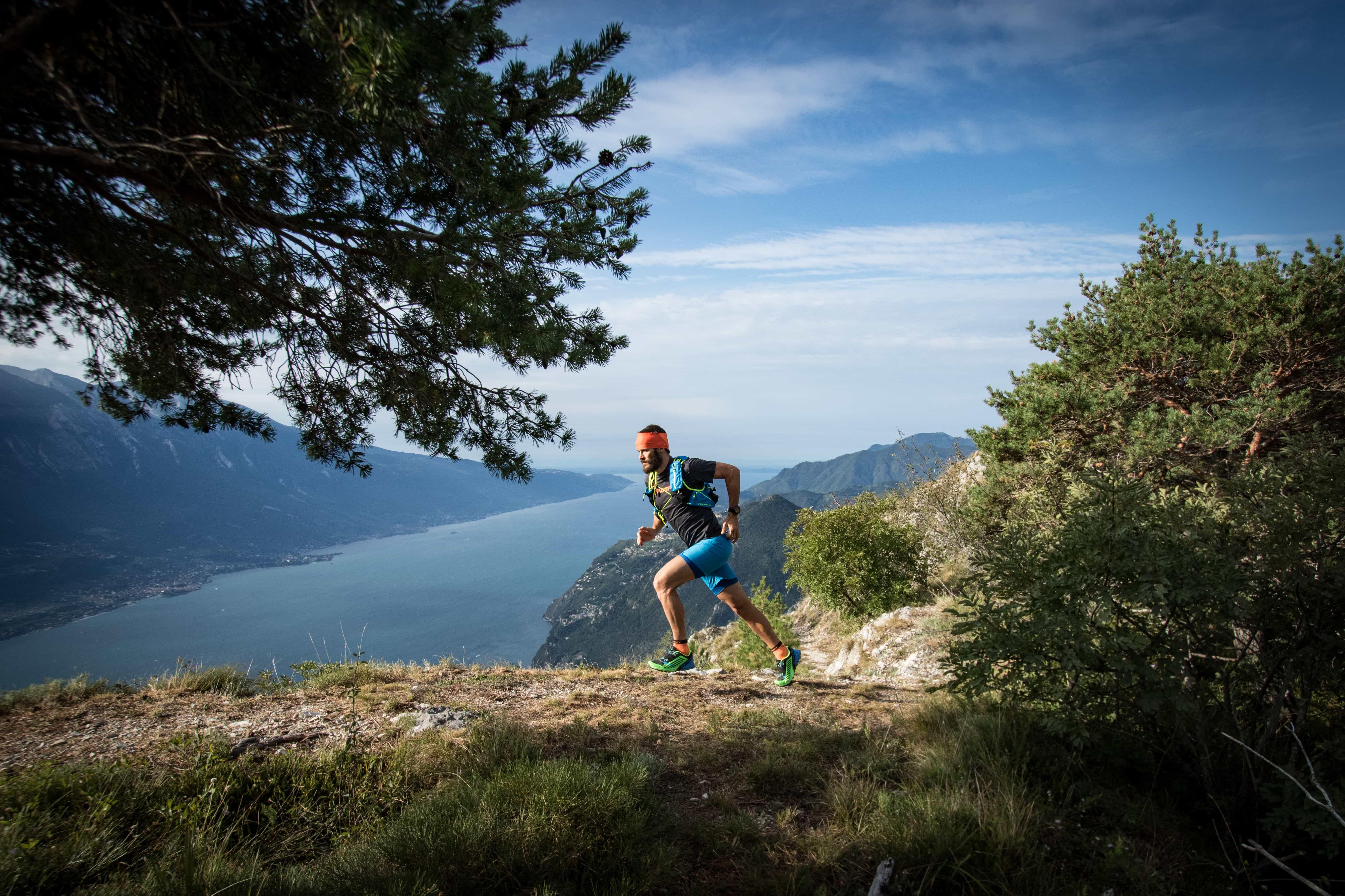 Sportlicher Mann joggt auf Bergpfad wischen Bäumen und Seeblick