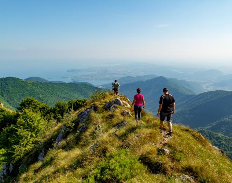 Drei Wanderer auf Bergkamm mit Panorama